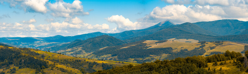 beautiful hilly countryside in autumn. beautiful weather with clouds on a blue sky above the distant mountain ridge with high peak. creative color toning applied