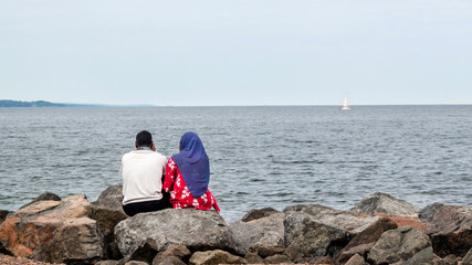 A Muslim couple are sitting on a rock to look at Lake Superior