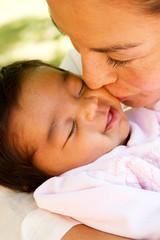 Hispanic mom kissing her new born baby.