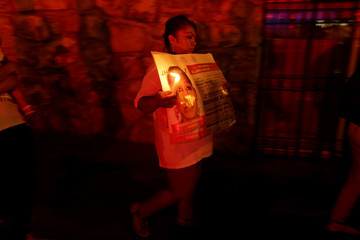 A relative holds a picture of a missing person during a vigil to mark International Day of the Victims of Enforced Disappearances in Ciudad Juarez