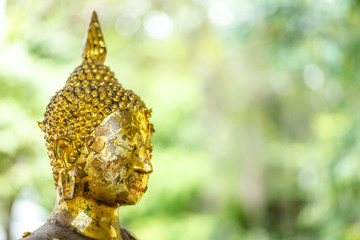 Buddha Statue with many gold leaf on face.