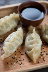 Close-up of steamed korean dumplings with sesame and soy sauce, selective focus, vertical shot