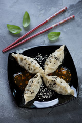 Black plate with steamed korean dumplings on a grey concrete background, high angle view, studio shot