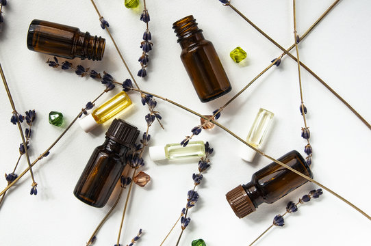Selection of essential oils, with herbs on white background. Brown and transparent Bottles