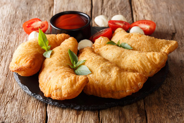 Hot fried panzerotti with a filling of tomatoes, herbs and mozzarella close-up are served on a board. horizontal