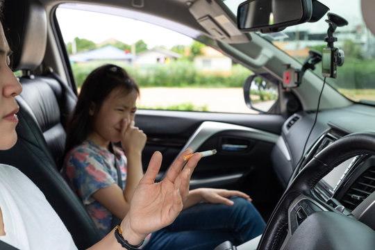 Asian woman smoking cigarette while driving inside the car and the child choking of smoke,stop smoking