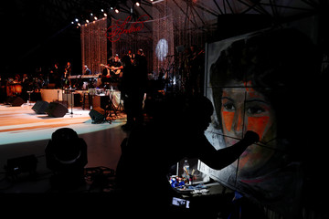 Demont Pinder paints a portrait of Aretha Franklin in real time during a free tribute concert to the late Aretha Franklin at Chene Park in Detroit, Michigan