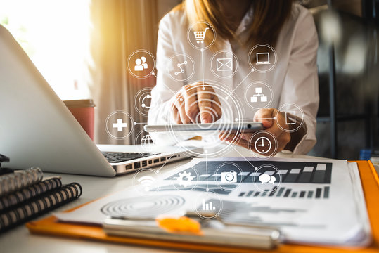 Digital marketing media in virtual screen.businesswoman hand working with mobile phone and modern compute with VR icon diagram at office in morning light