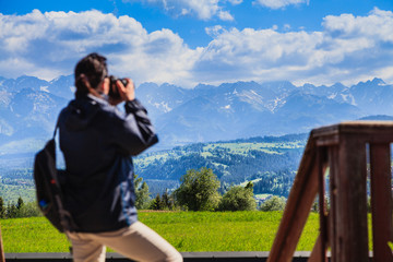Tourist in the mountains photographing beautiful views. Focus on the landscape.