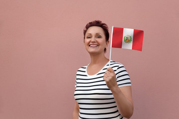 Peru flag. Woman holding Peru flag. Nice portrait of middle aged lady 40 50 years old with a national flag over pink wall background outdoors.