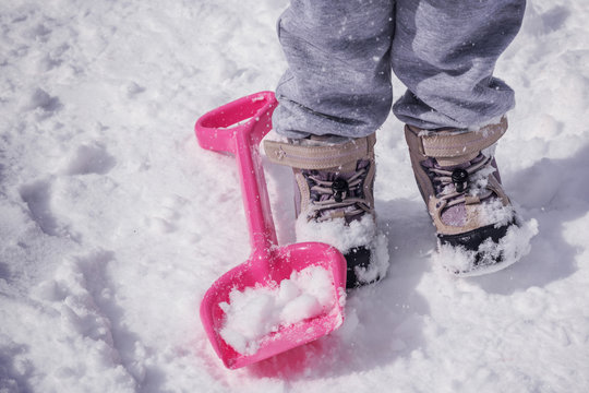 Legs of a child in winter boots and a red shovel in the snow, open air, close-up