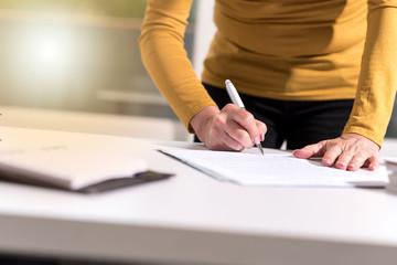 Businesswoman signing document, light effect