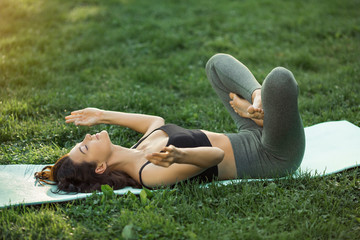 Funny photo about young woman doing yoga exercise and fooling around outdoors in park at morning. Cheerful girl practicing yoga smiling making funny pose. Mixed race Asian Caucasian young model