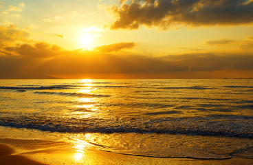 Colorful dawn with sun through clouds rays over sea and sandy shore. Nature composition.