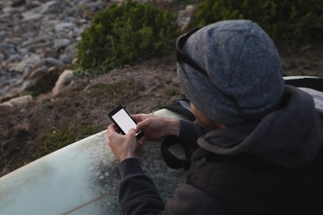 Man with surf board using mobile on the beach