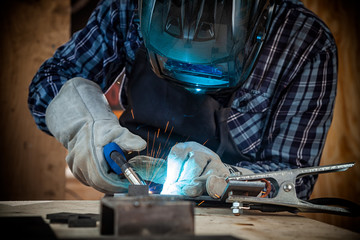 Close up of a young  man welder in  uniform, welding mask and welders leathers, weld  metal  with a arc welding machine  in workshop, blue and orange  sparks fly to the sides