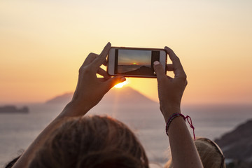 Woman taking photos of a sunset wit a mobile phone