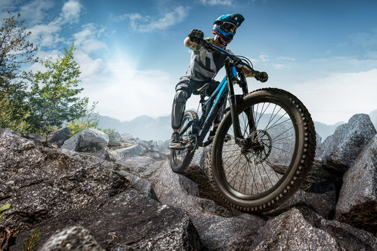 Mountain biker on stone trail. Male cyclist rides the rock