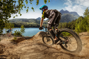 Two bikers on mountain trail near the lake. Male cyclists rides the rock. Mountain Bike. Cross-Country Cycling Wall mural