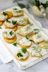 Snack from crackers and curd fish paste with herbs on a light background.