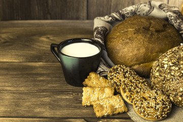 Food. Country breakfast. Assortment of fresh bread baked in a bakery, biscuits and a mug with milk on a wooden table background