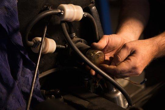 Male mechanic servicing a car