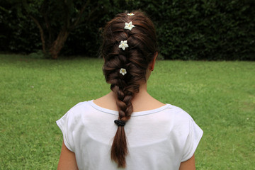 Girl with hair braided and solanum jasmin fresh flowers in braid