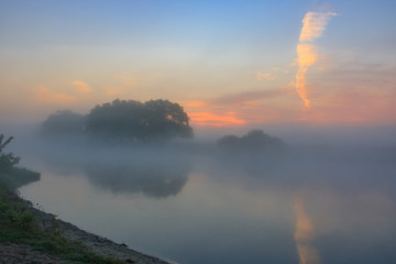 Fog above the river surface on a sunny summer morning. River landscape