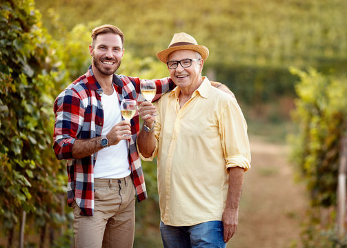 smiling father and son tasting wine in vineyard.