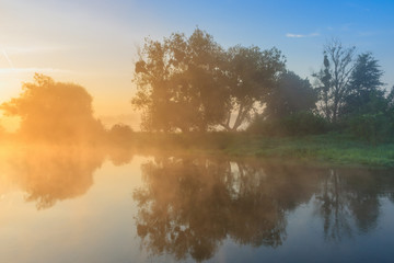 Fog over river surface in orange sunrise. River landscape in summer morning