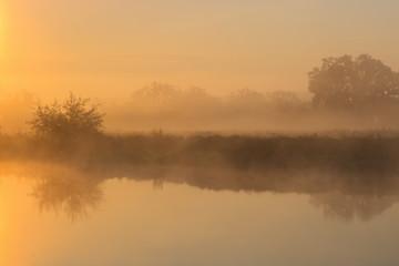 Orange sunrise over river surface with fog. River landscape in summer morning