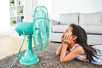 happy kid lying down in front of electric fan.