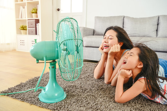 mother and daughter lying in front of fan.