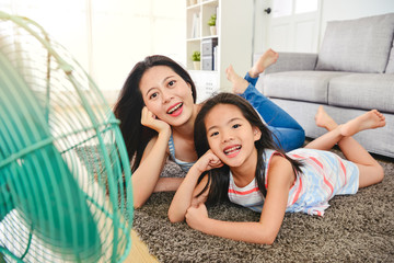 happy asian mom and kid cooling faces by fan.