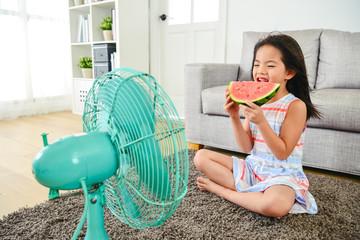 cute little girl enjoying a slice of melon.