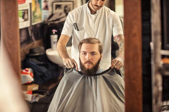Barber put on apron around customer.