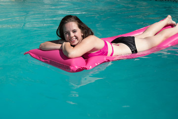 Cute white girl relaxing on a pink raft in a backyard swimming pool on a sunny summer day.  Girl sunbathing on a raft in a swimming pool in a backyard in the sun looking at camera smiling.