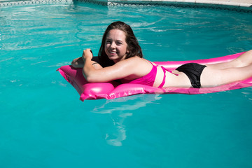 Cute white girl relaxing on a pink raft in a backyard swimming pool near a diving board on a sunny summer day.  Girl sunbathing on a raft in a swimming pool in a backyard in the sun.