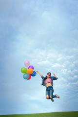 Asain woman holding colorful balloons and jumping in to blue sky  and white clouds background.