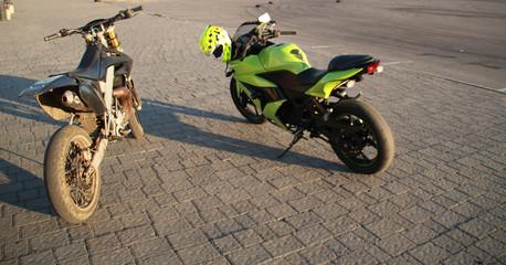 Green sport motorbike and black motard  on the background of gray asphalt. Motorcycle on the parking lot. Sunset. Ukraine, Lviv