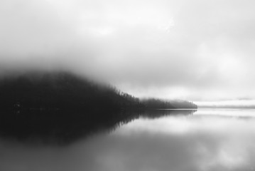 Delightful landscape view of Austrian Alps. Monochromatic sunset over the early morning river covered with fog.