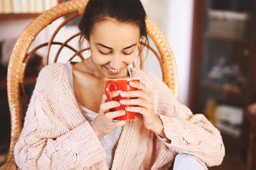 Soft photo of woman in a wicker chair with old book and cup of coffee