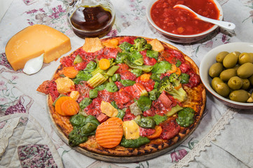 Vegetarian vegetable pizza with various colored cheeses on a wooden platter.
