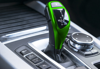 Green Automatic gear stick of a modern car. Modern car interior details. Close up view. Car detailing. Automatic transmission lever shift. Black leather interior with stitching.