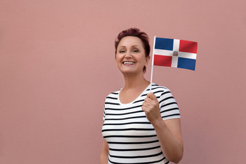 Dominican Republic flag. Woman holding Dominican Republic flag. Nice portrait of middle aged lady 40 50 years old with a national flag over pink wall on the street outdoors.