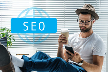 bearded developer in hat holding coffee to go and using smartphone with SEO sign