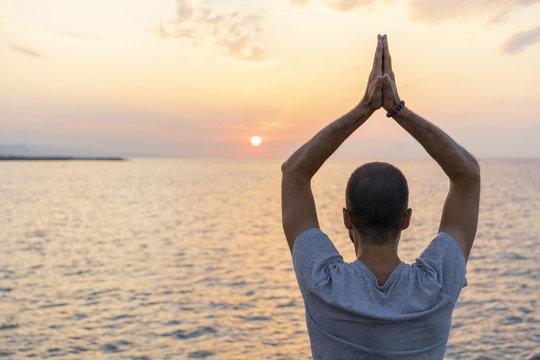 Spain. Man doing yoga during sunrise, raising arms, rear view