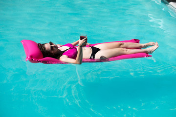 Pretty woman in a black and pink bikini and aviator sunglasses having a cocktail in an outdoor swimming pool on a bright pink raft. Woman floating in the swimming pool on raft in the summer sun.