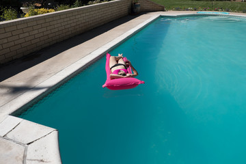 Pretty woman in a black and pink bikini and aviator sunglasses having a cocktail in an outdoor swimming pool on a bright pink raft. Woman relaxing in the swimming pool on raft in the summer.