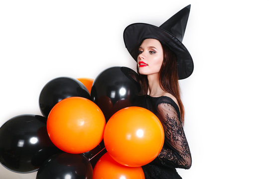 Portrait of beautiful young woman in black witch halloween costume with orange and black balloons over white background